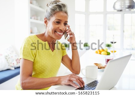 Woman Using Laptop And Talking On Phone In Kitchen At Home - stock photo