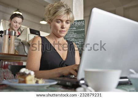 Woman Using Laptop at Cafe - stock photo