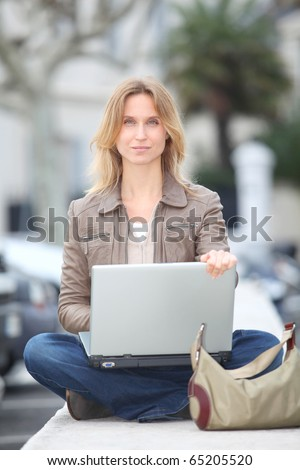 Woman using laptop computer in town - stock photo