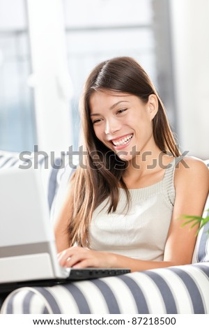 Woman using laptop computer smiling happy sitting in sofa. Pretty mixed race Caucasian Asian female model at home.