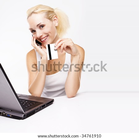 Woman using laptop, holding credit card and making an order via phone