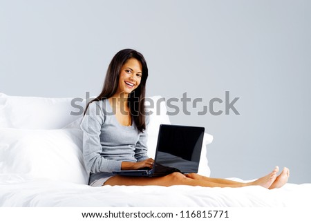 woman using laptop in bed at home, leisure lifestyle concept - stock photo