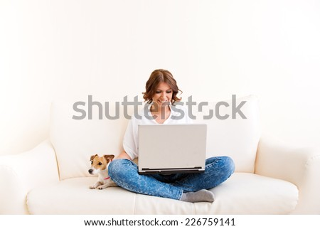 Woman using laptop on the sofa - stock photo