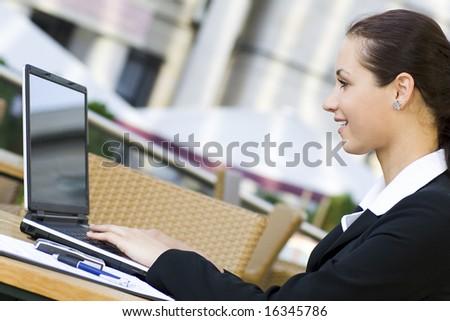 Woman using laptop outdoors - stock photo