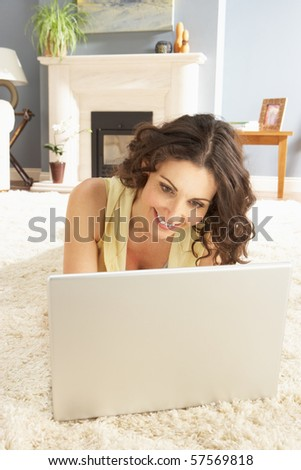 Woman Using Laptop Relaxing Laying On Rug At Home - stock photo