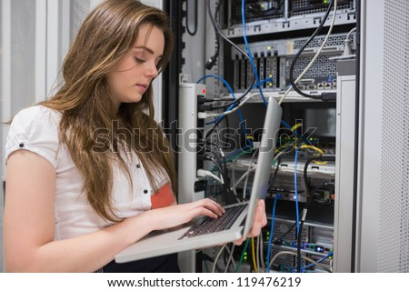 Woman using laptop to work on servers in data center - stock photo