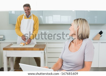 Woman using laptop while man chopping vegetables in the kitchen at home