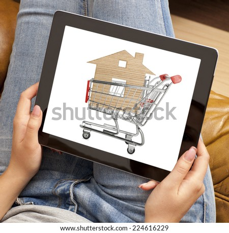 Woman using laptop with online shopping cart on screen - stock photo