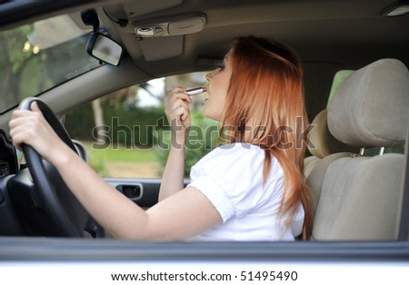 Woman using lipstick during driving