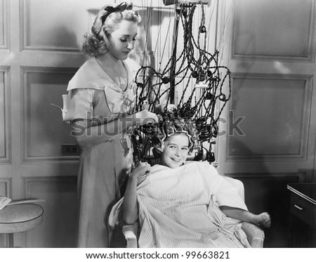 Woman using machine to style teenage girls hair - stock photo