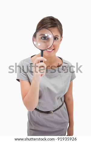 Woman using magnifier against a white background - stock photo