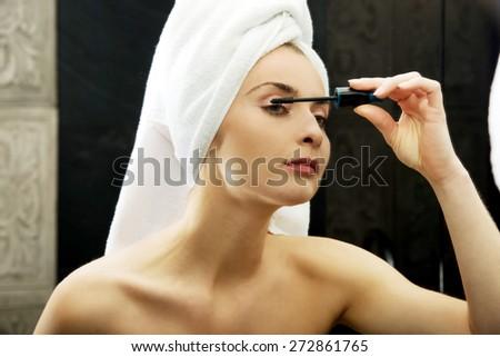Woman using mascara in bathroom mirror. - stock photo