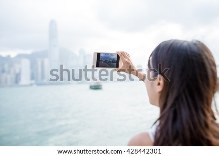 Woman using mobile phone for taking photo - stock photo