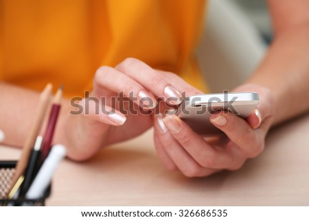 Woman using mobile phone on workplace close up