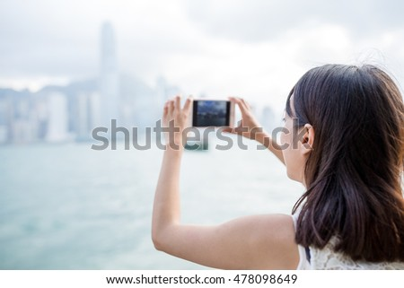 Woman using mobile phone to take photo