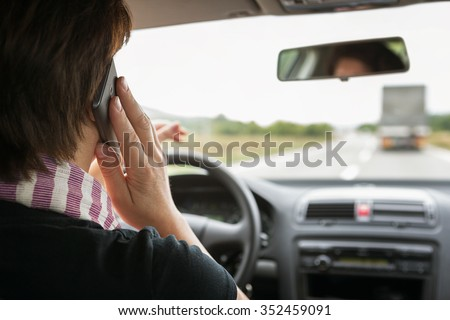 Woman using mobile phone while driving a car - stock photo