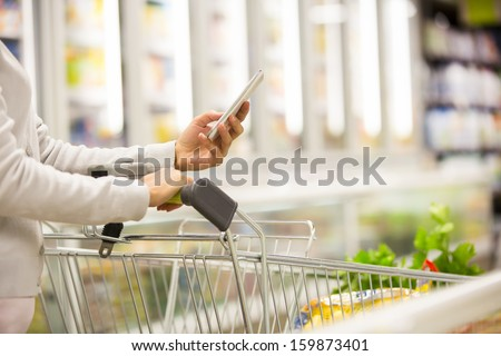 Woman using mobile phone while shopping in supermarket, trolley, frozen department store - stock photo