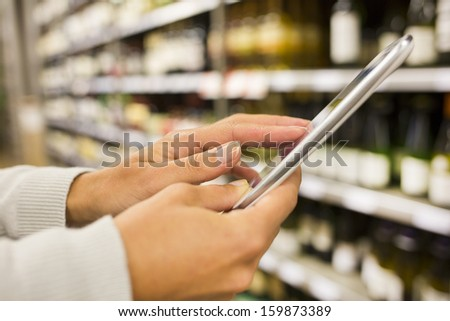 Woman using mobile phone while shopping in supermarket, wine department store - stock photo