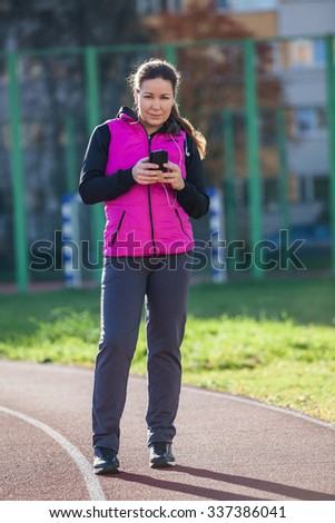Woman using mobile phone while standing at the stadium lane, looking at camera - stock photo