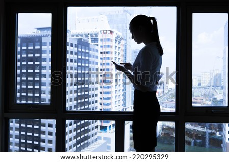 Woman using mobile smart phone in the office - stock photo