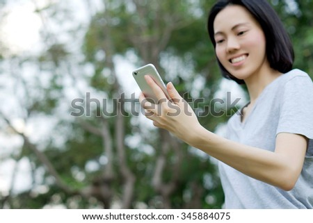 woman using mobile smart phone in the park