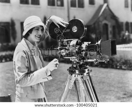 Woman using movie camera outdoors - stock photo