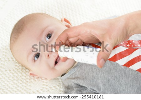 Woman using nasal spray for baby - stock photo