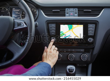 Woman using navigation system while driving a car - stock photo