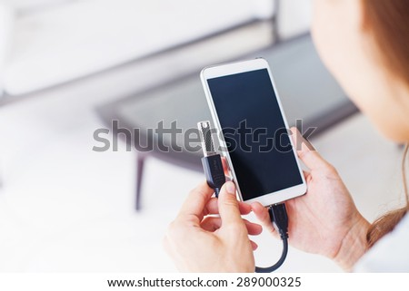 woman using otg usb with her mobile phone to copy photos - stock photo