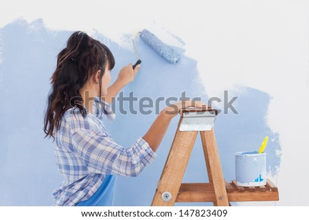 Woman using paint roller to paint wall in blue paint leaning on ladder - stock photo