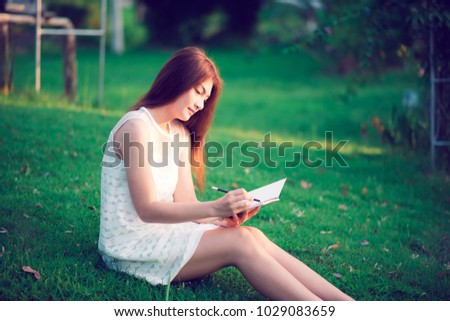 woman Using pencil and book in garden