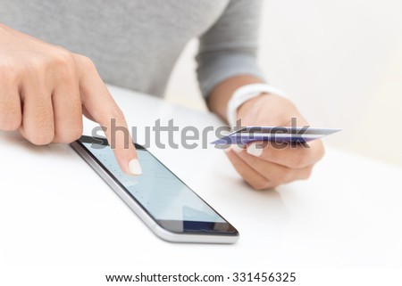 woman using phone and credit card shopping online - stock photo
