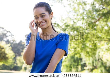 Woman using phone in park on a sunny day