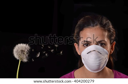 Woman using protective mask from spring allergy season dandelion pollen plant. - stock photo