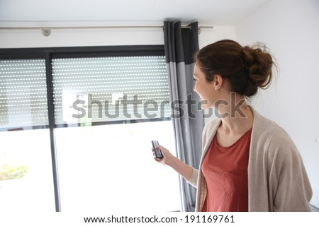 Woman using remote control to open electric shutter - stock photo