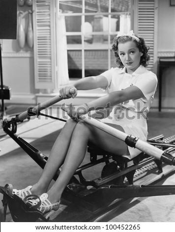 Woman using rowing machine - stock photo