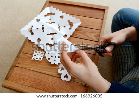 Woman using scissors to cut folded white paper into snowflake designs - stock photo