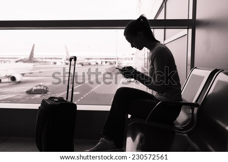 Woman using smart phone mobile at the airport - stock photo