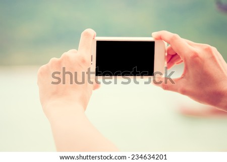 Woman using smart phone take a photo (selfie) on the beach during vacation in Thailand. Vintage style. - stock photo