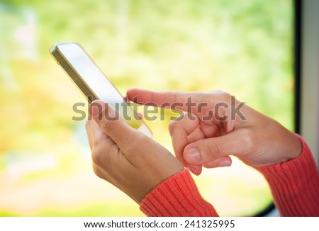 Woman using smart phone while traveling by train - stock photo