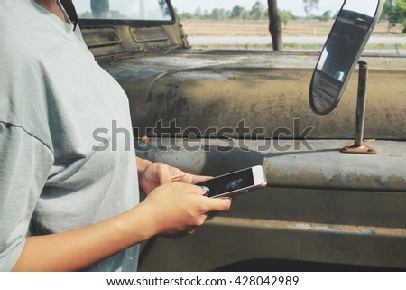 Woman using smart phone with car