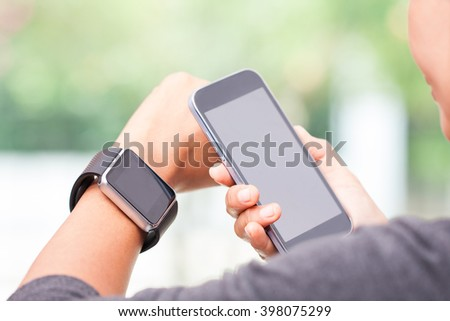 Woman using smart watch and smart phone. - stock photo