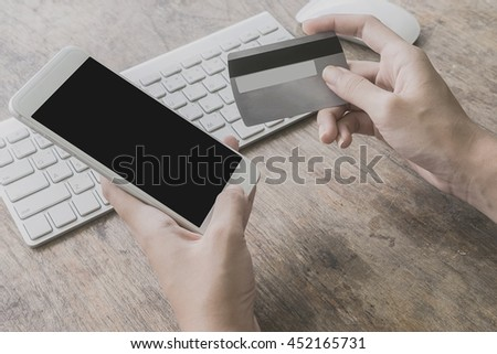 woman using smartphone and computer to online shopping and pay by credit card, Low light, selective focus on hand, can be used for e-commerce, business, technology and internet concept, Vintage tone - stock photo