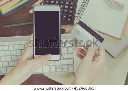 woman using smartphone and computer to online shopping and pay by credit card, Low light, selective focus on hand, can be used for e-commerce, business and technology concept, Vintage tone filter - stock photo