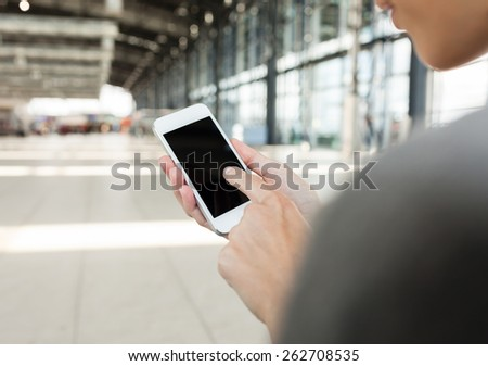 Woman using smartphone at airport - stock photo
