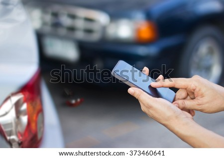 woman using smartphone at roadside after traffic accident, soft focus - stock photo