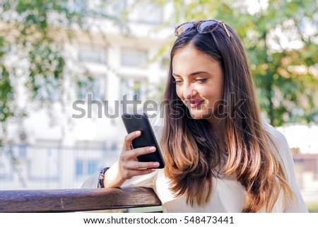 Woman using smartphone in the city. Hipster girl browsing Internet on a phone, texting and communicating