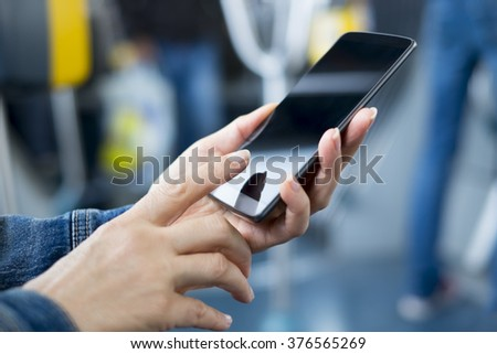 Woman using smartphone on bus. Sms, message, app - stock photo