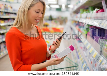Woman using smartphone to compare prices in supermarket  - stock photo
