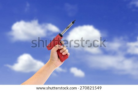 Woman using soldering tool on blue sky background. - stock photo